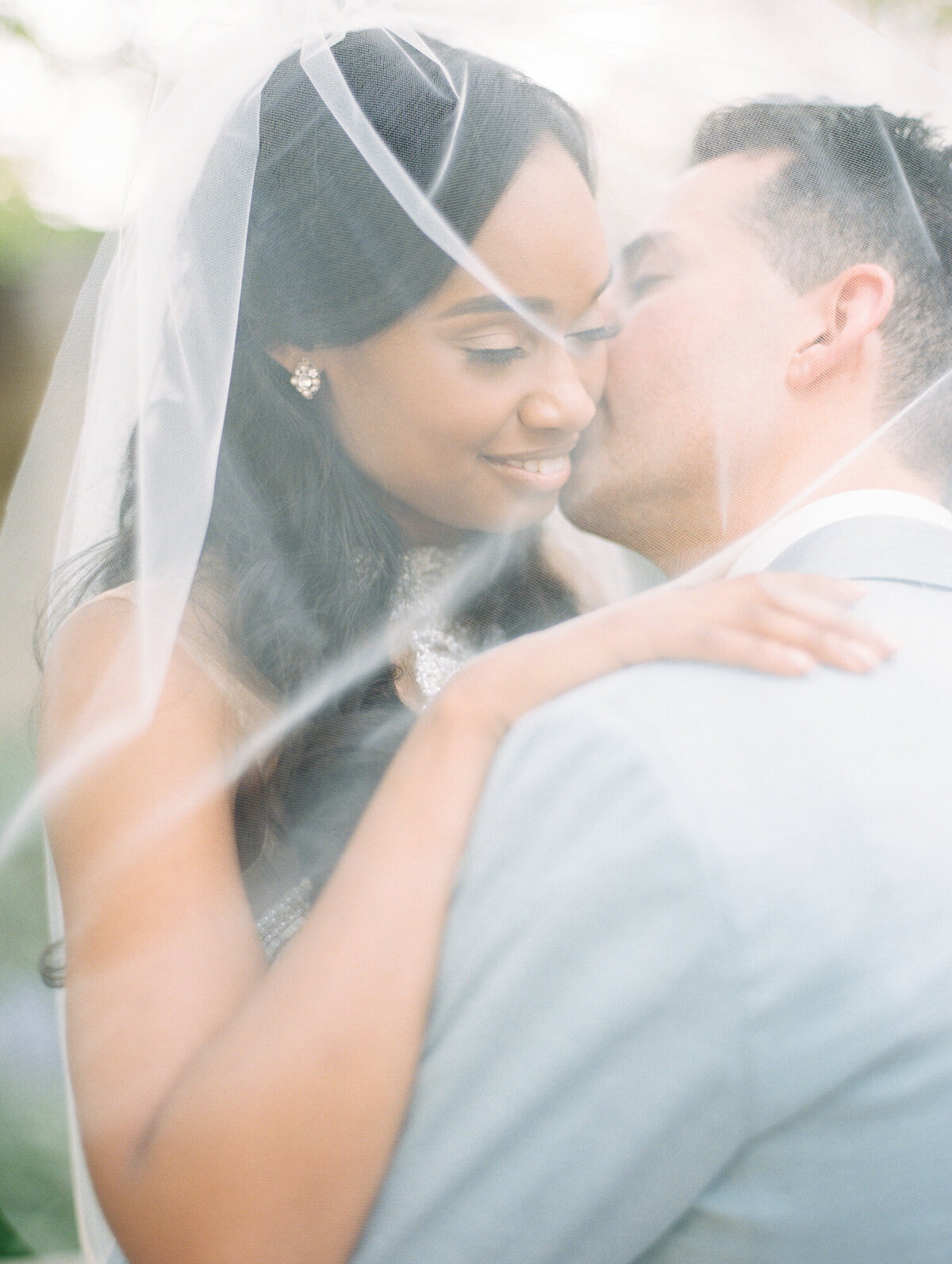 Groom kissing bride underneath veil