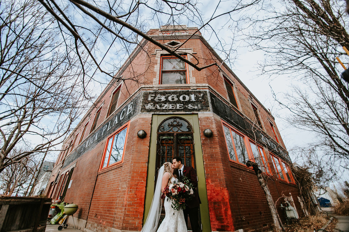 wedding couple kissing in front of building in RINO district in Denver Colorado