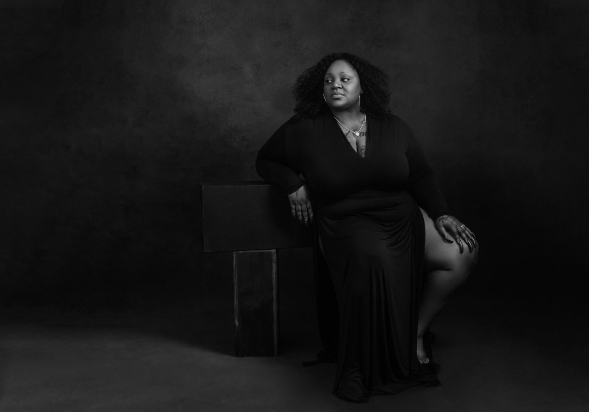 An African American black woman in a black dress reclines for a black and white picture at Janel Lee Photography studios in Cincinnati Ohio