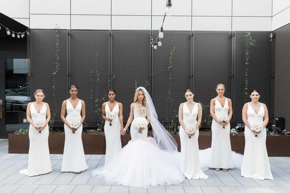 Lovely bride and her maids in all white with bouquets by Flora Nova Design Seattle