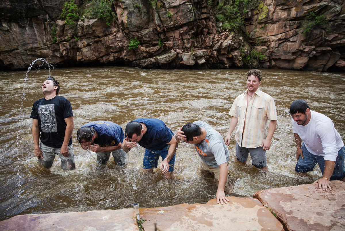 Fun photo of a groom and his best friends bathing in the Saint Vrain river at River Bend in Lyons Colorado