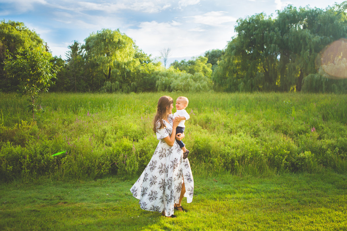mother spinning with her baby son in sunny field {Oakville Family Photographer}