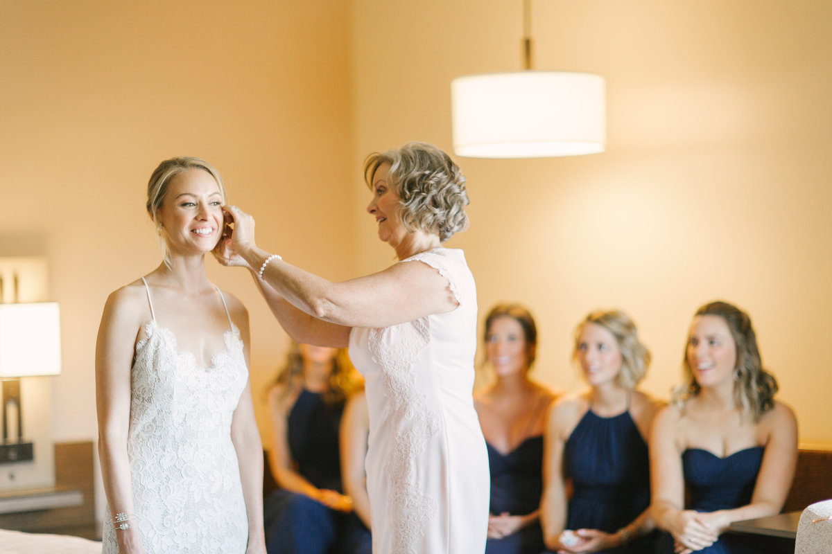 Mother of the bride helps daughter put on earrings prior to Firestone Winery wedding