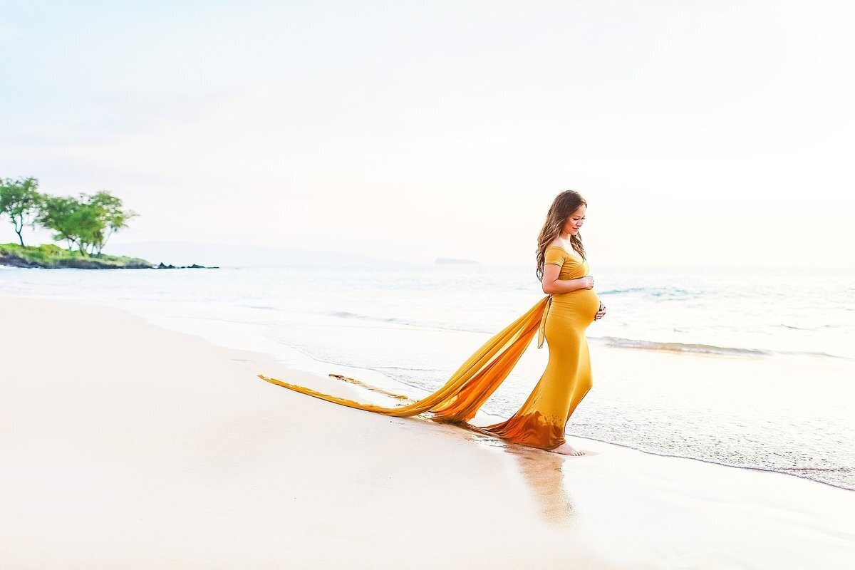 Pregnant woman in gold maternity gown with train walks on Maluaka Beach in Maui