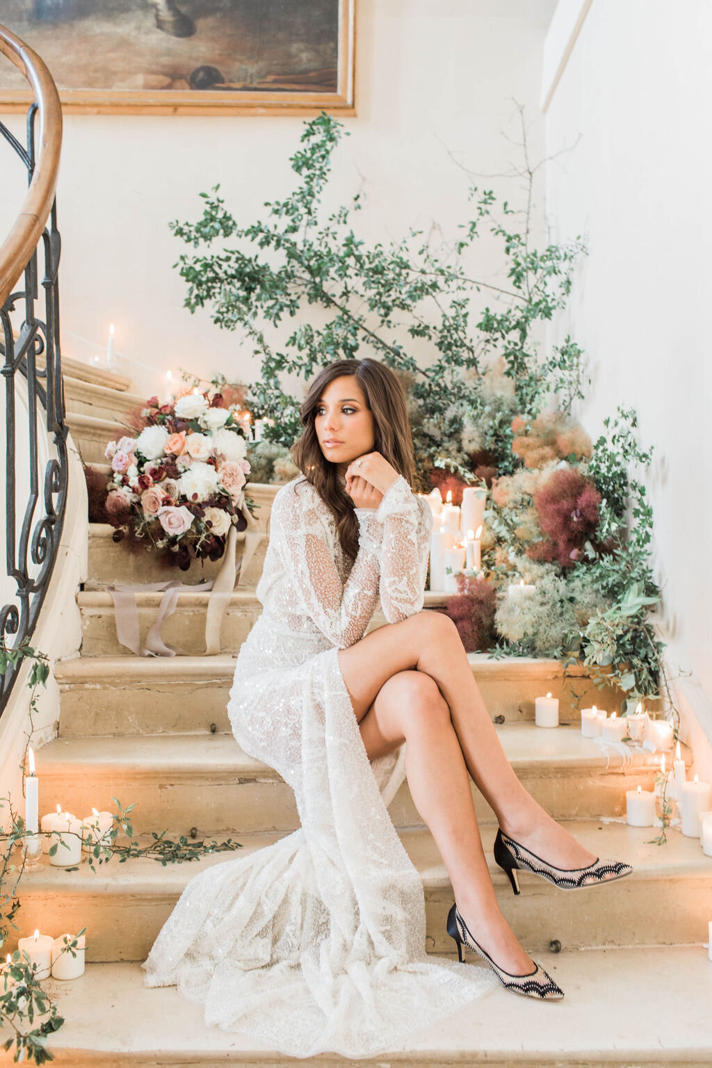 Bride posed on staircase at chateau wedding venue
