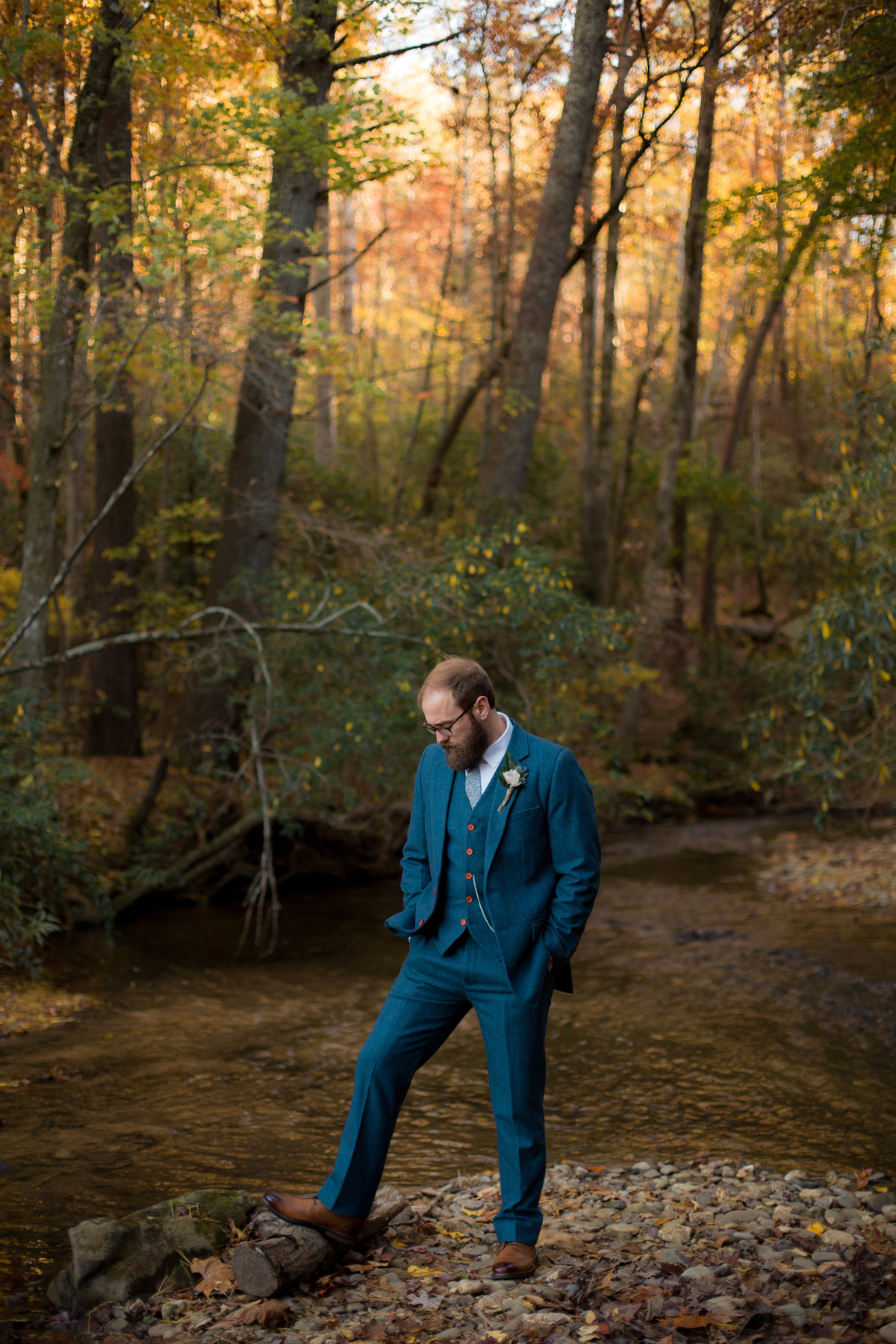 trendy groom with beard photographed in river