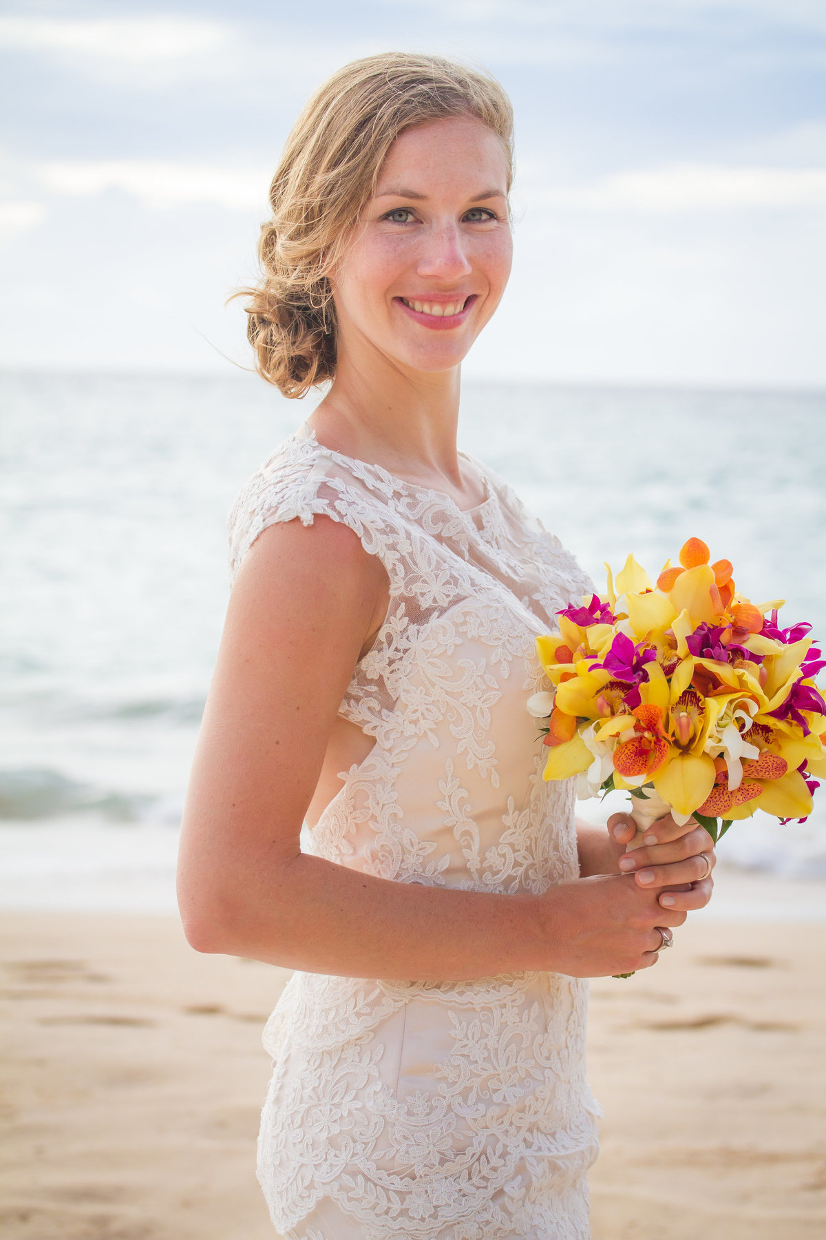 Lovely bride with lace dress and tropical bouquet on Kauai beach.
