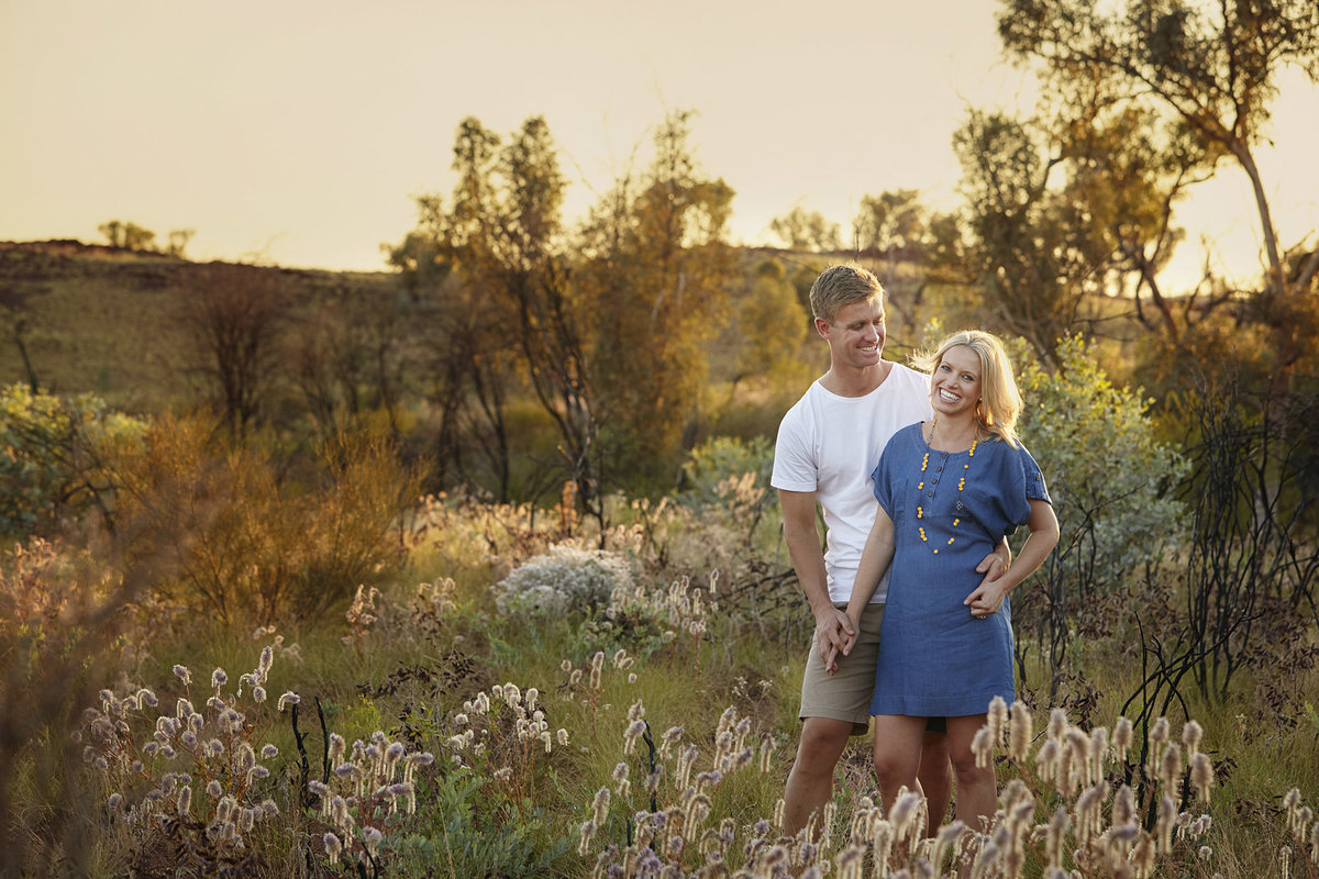 Husband looking at wife and wife looking at camera smiling with golden sunlight streaming through and natural bush and mountains in the background