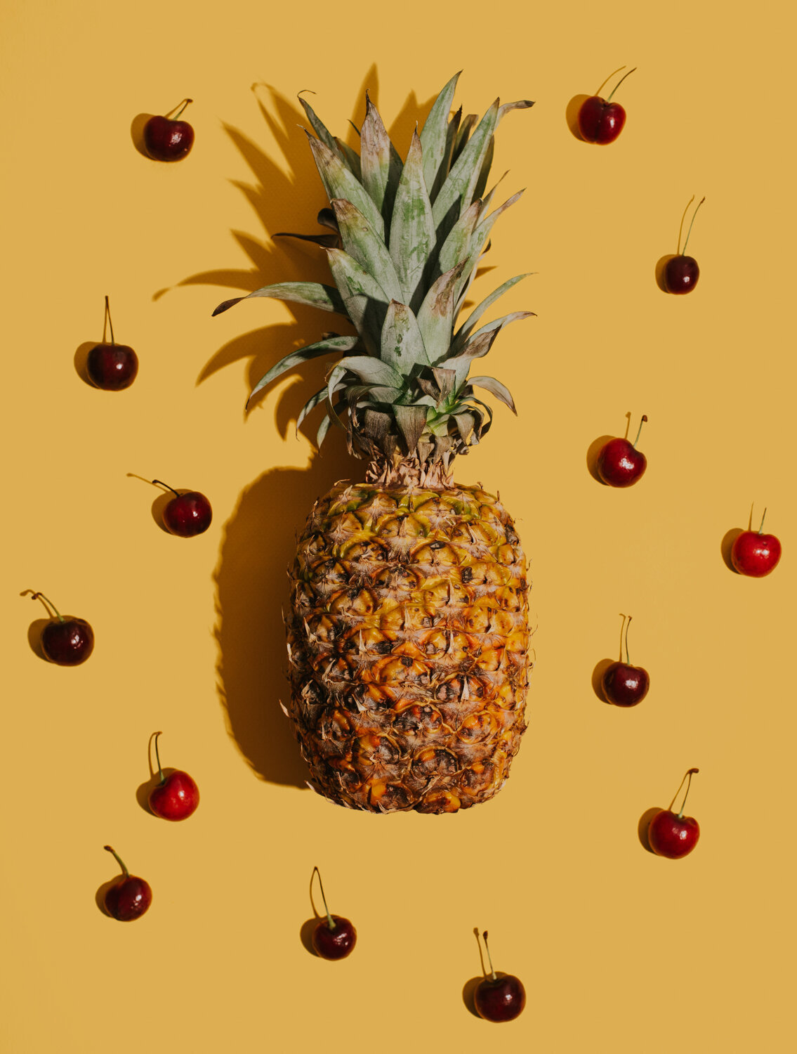 pineapple and cherries on yellow