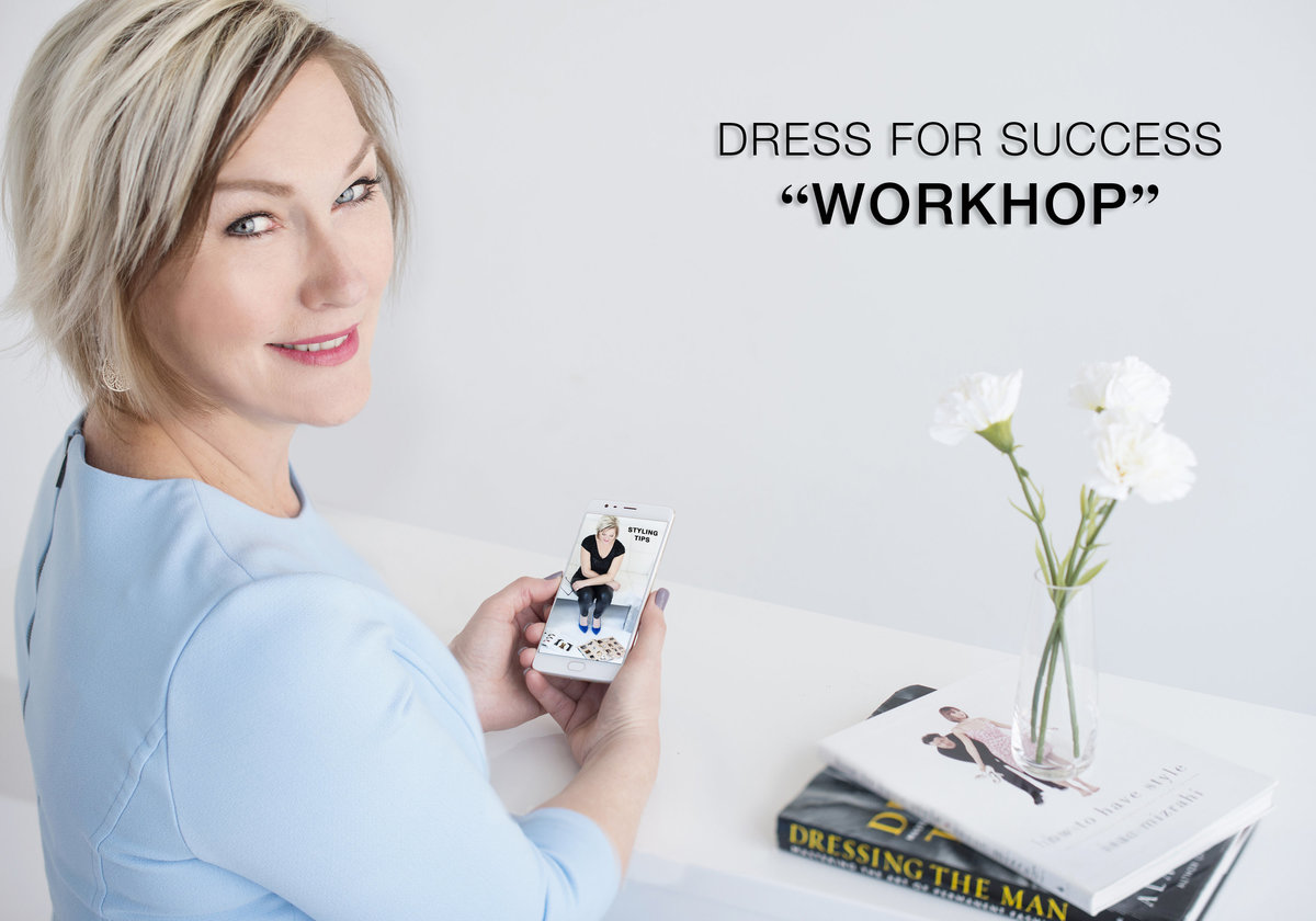 woman checking her business card wearing blue dress sitting on desk warm , happy and  approachable  with short blond hair