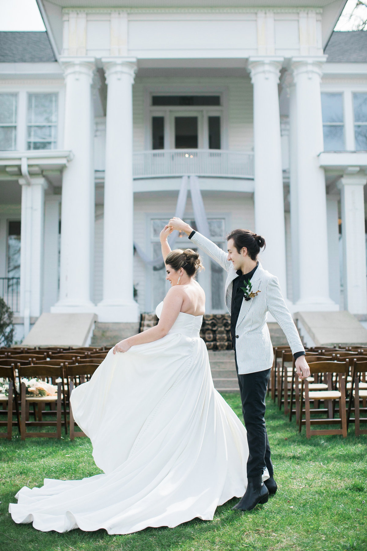 Wedding Photographer, bride and groom dancing outside of estate building