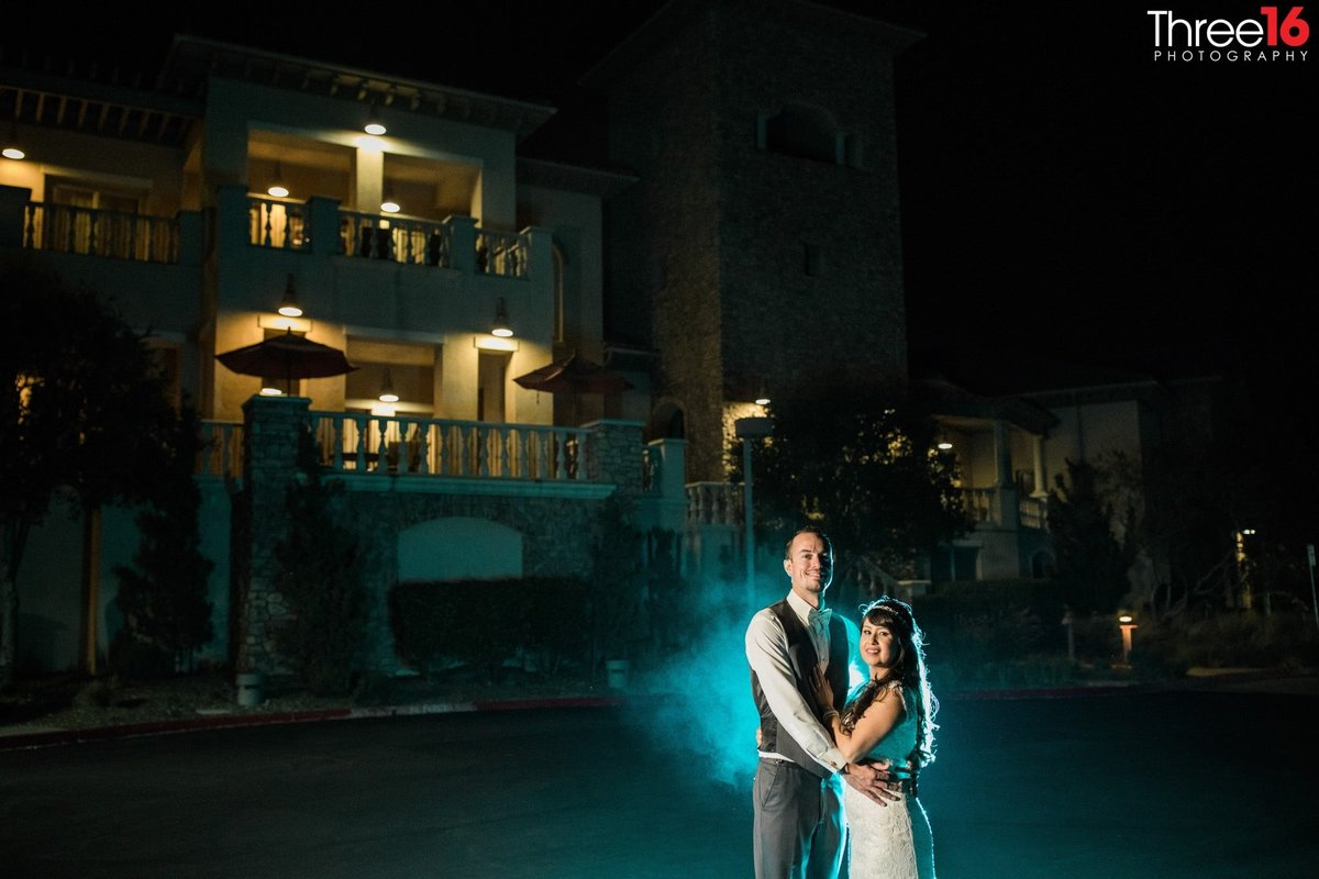 Bride and Groom pose together at night with special effect in background