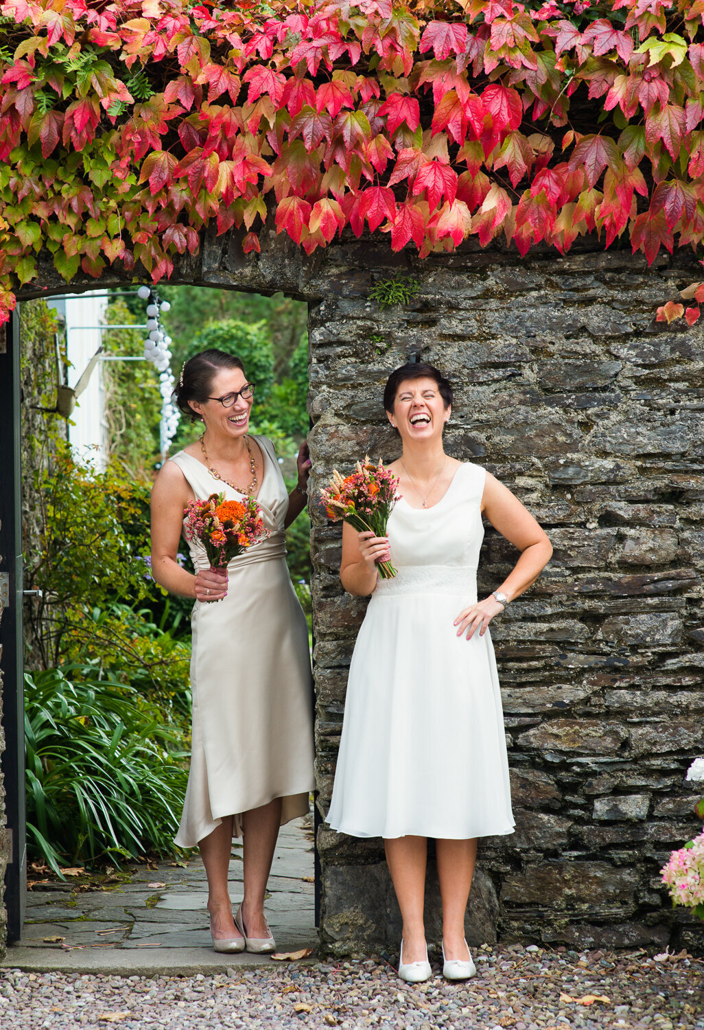 Gay brides holding orange flower bouquets, laughing underneath red and orange ivy leaf