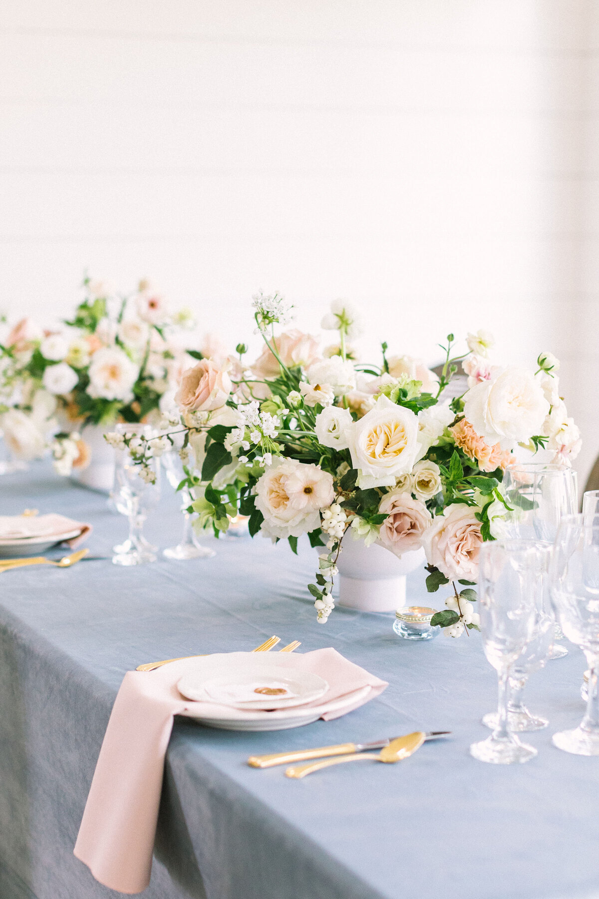 A beautiful table scape with white and pink floral arrangements