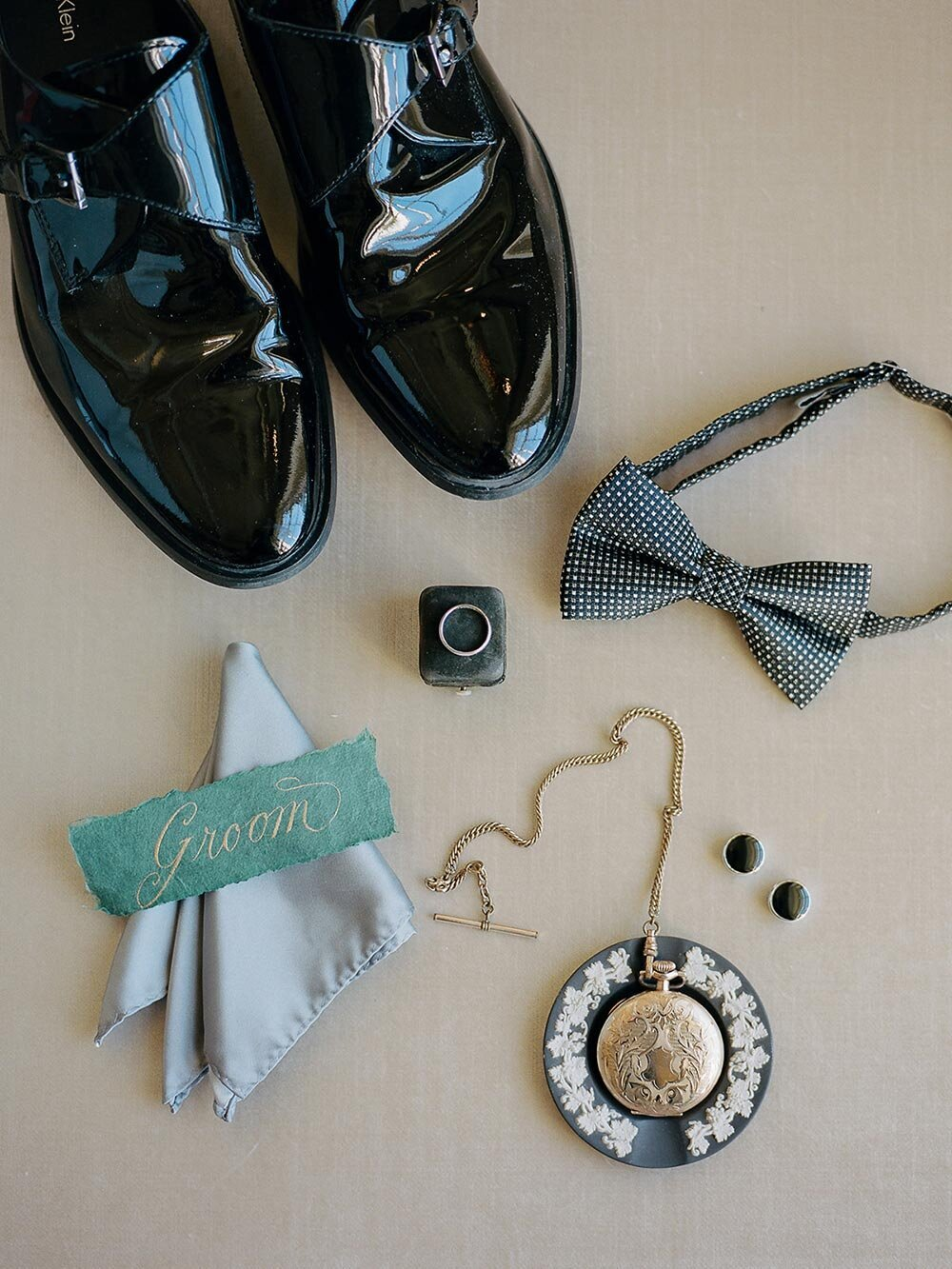 Flatlay of groom's wedding day shoes, hankerchief and patterned bow tie