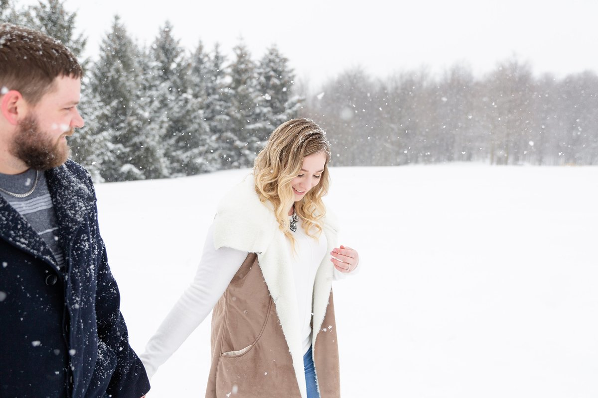Guy-looks-towards-his-future-wife-as-they-walk-through-the-snow-together-at-their-engagement-session