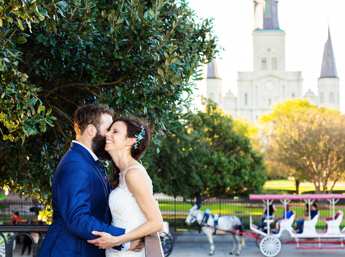 bride and groom laughing with St. Louis Cathedral in the background