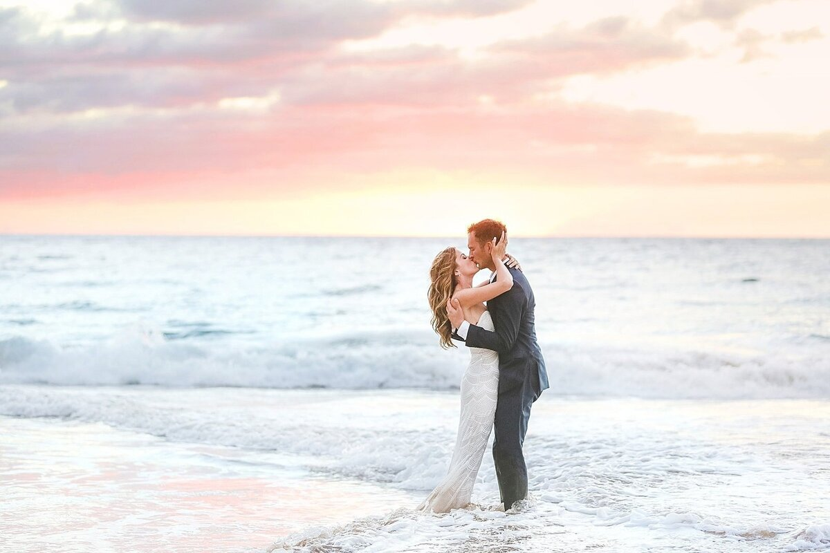 Eloping couple share a kiss on the shoreline after their intimate beach wedding on Maui