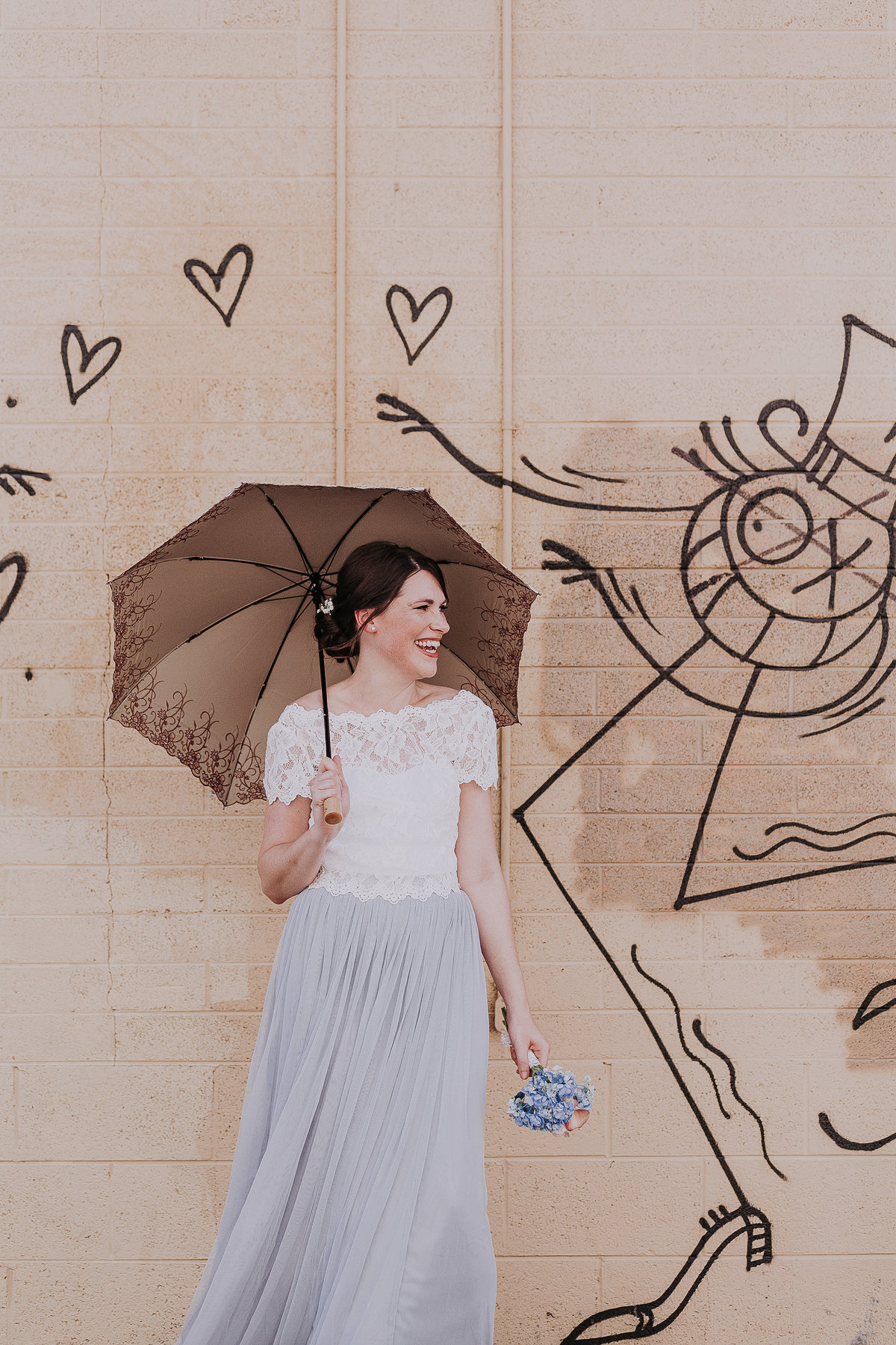 Reno wedding photographers bride poses near graffiti wall