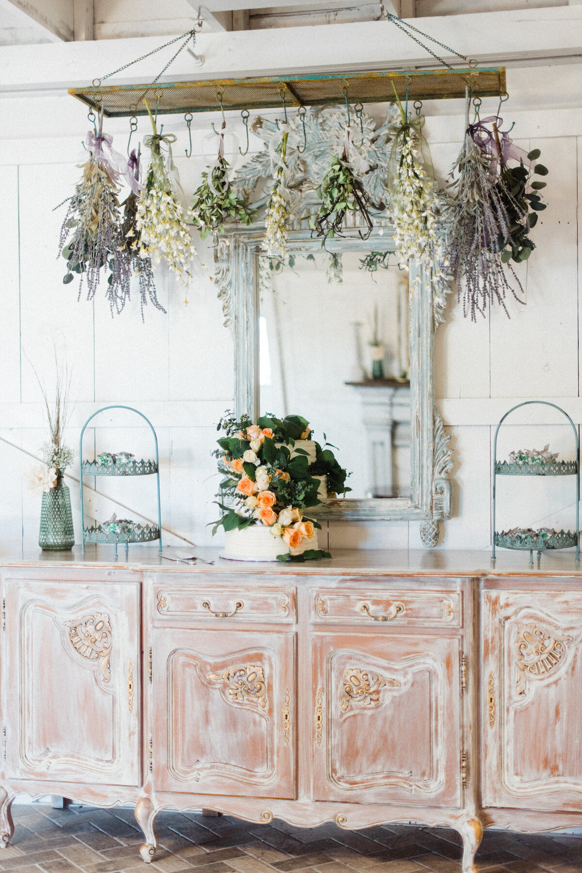 Rustic bar table set up with hanging dried florals and a wedding cake