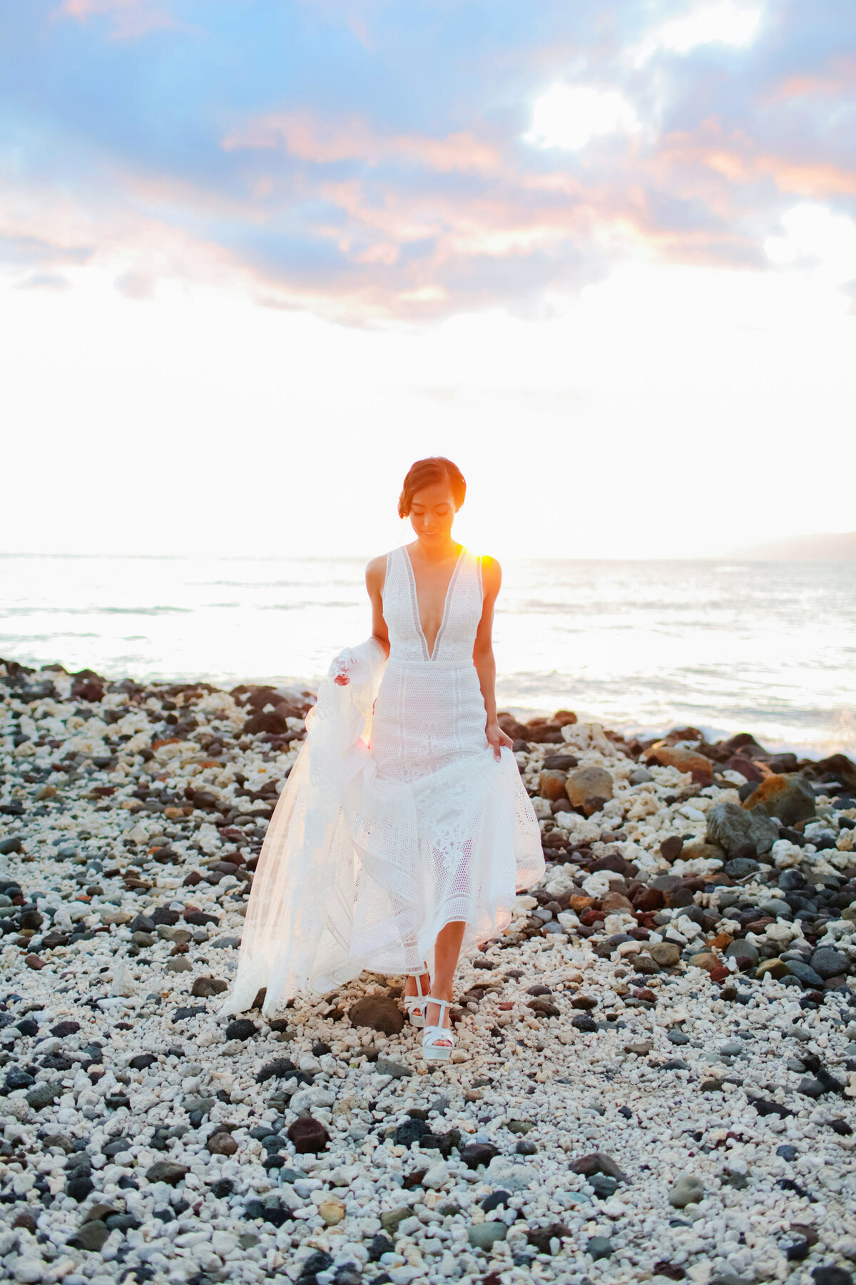 Bride at Olowalu Plantation House holding gown and waking on jetty