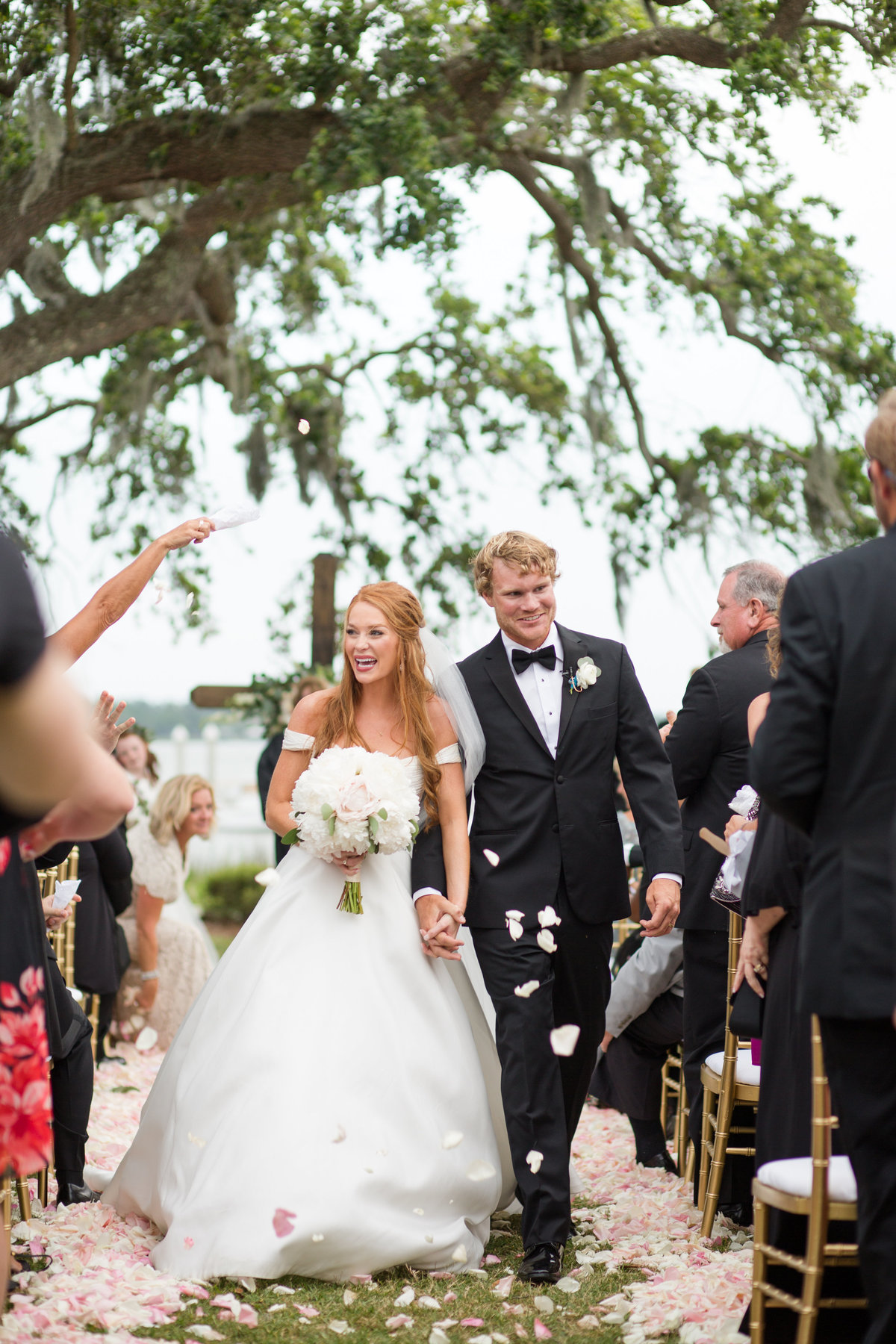 bride and groom walking down aisle with rose petals thrown at them. savannah yacht club wedding.