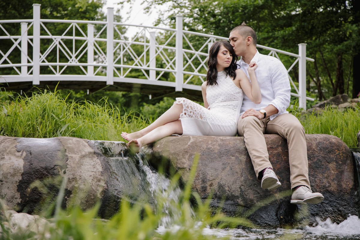 engaged couple sits by stream at sayen gardens