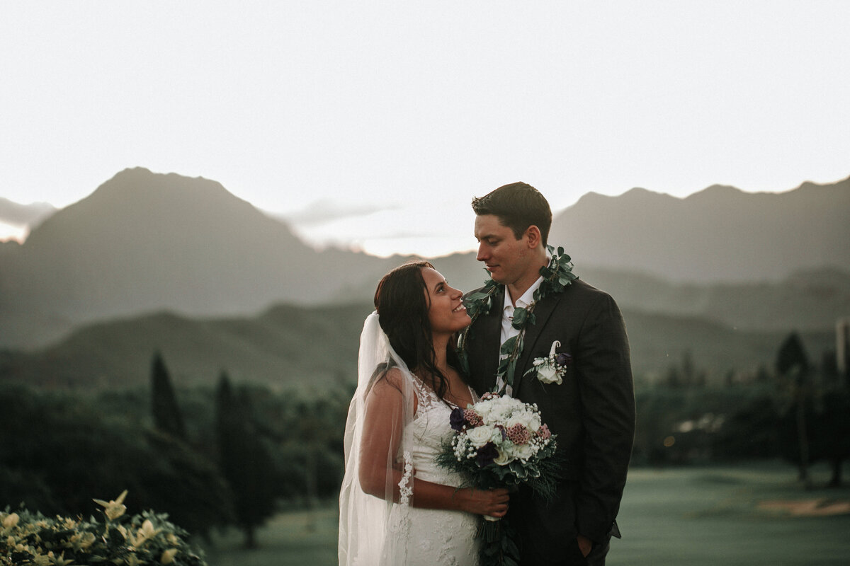 Bride and groom smiling at each other overlooking beautiful golf course mountain scenery at country club