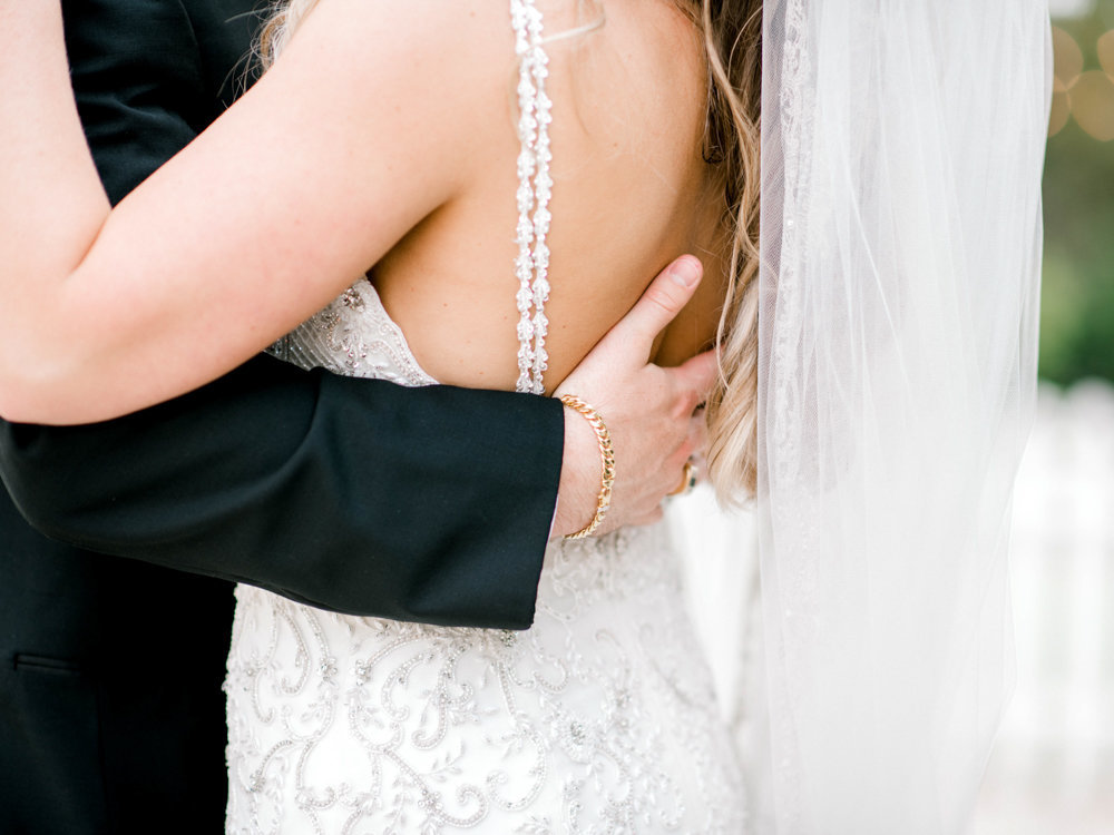 Groom places hand on brides back Tybee Wedding Chapel