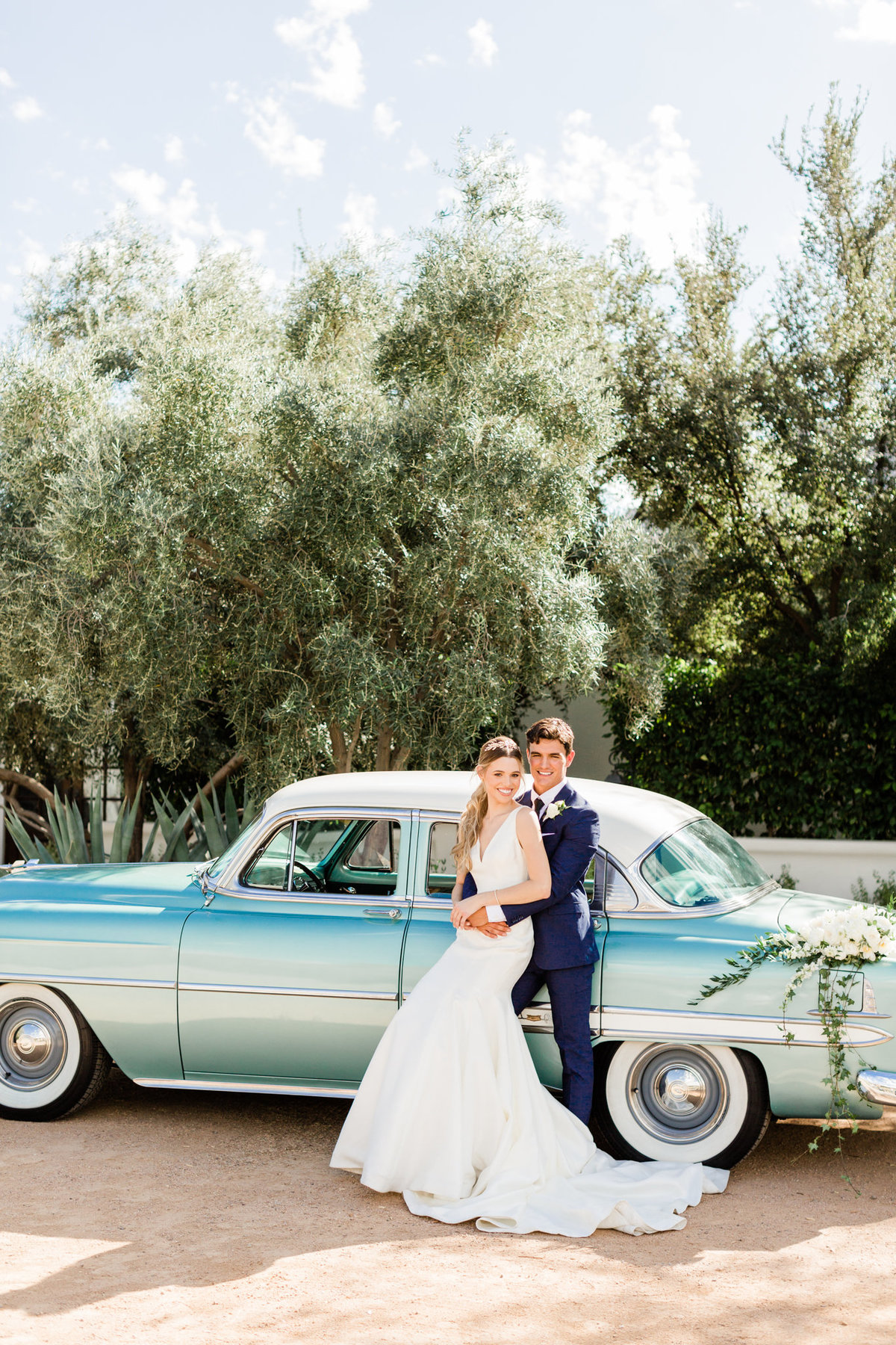 newlywed couple embracing in front of a classic teal blue car at el chorro