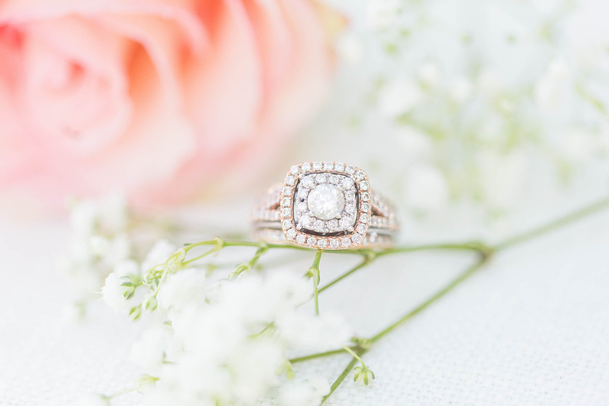 Halo cut ring surrounded by pink rose and babys breath