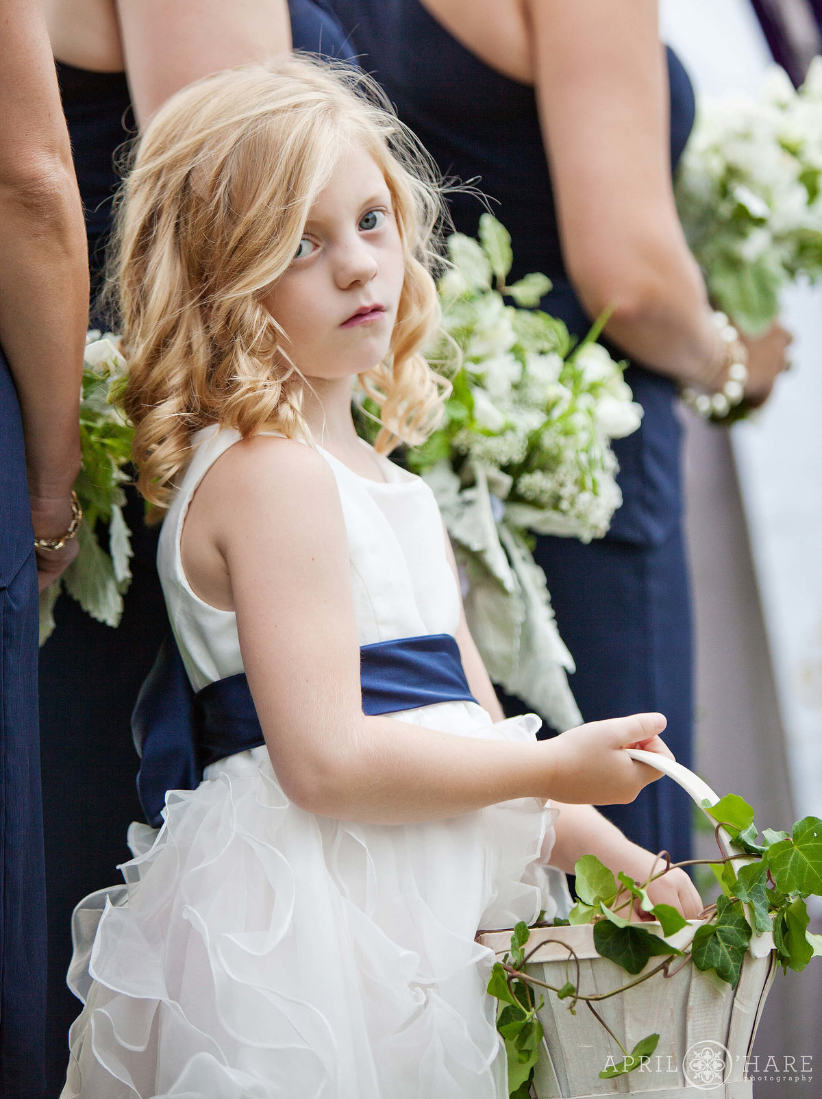 Serious flower girl during outdoor wedding ceremony in Boulder Colorado