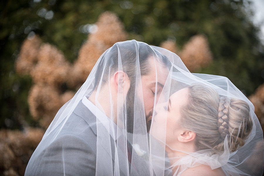 A bride and groom kiss under a veil