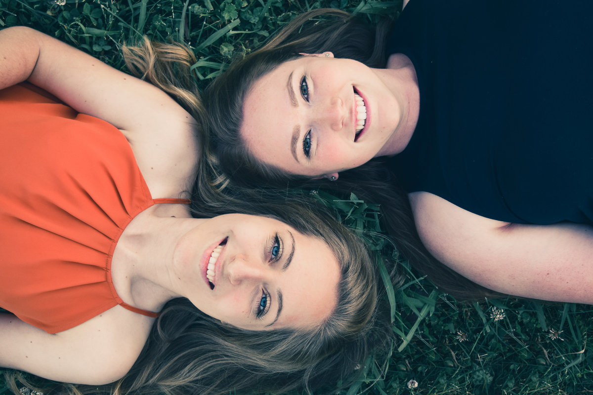 two girls lying in grass looking up at camera