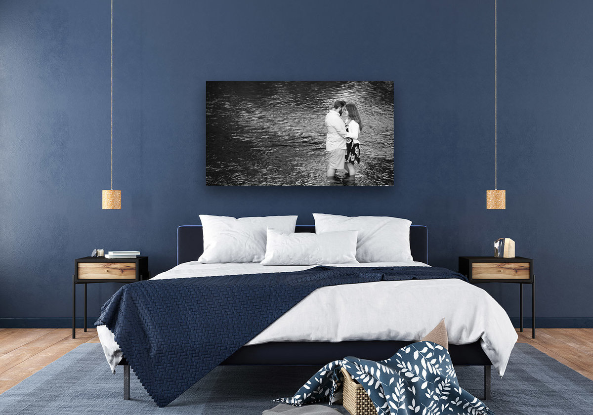 Wide fine-art print on a blue wall above the bed frame.