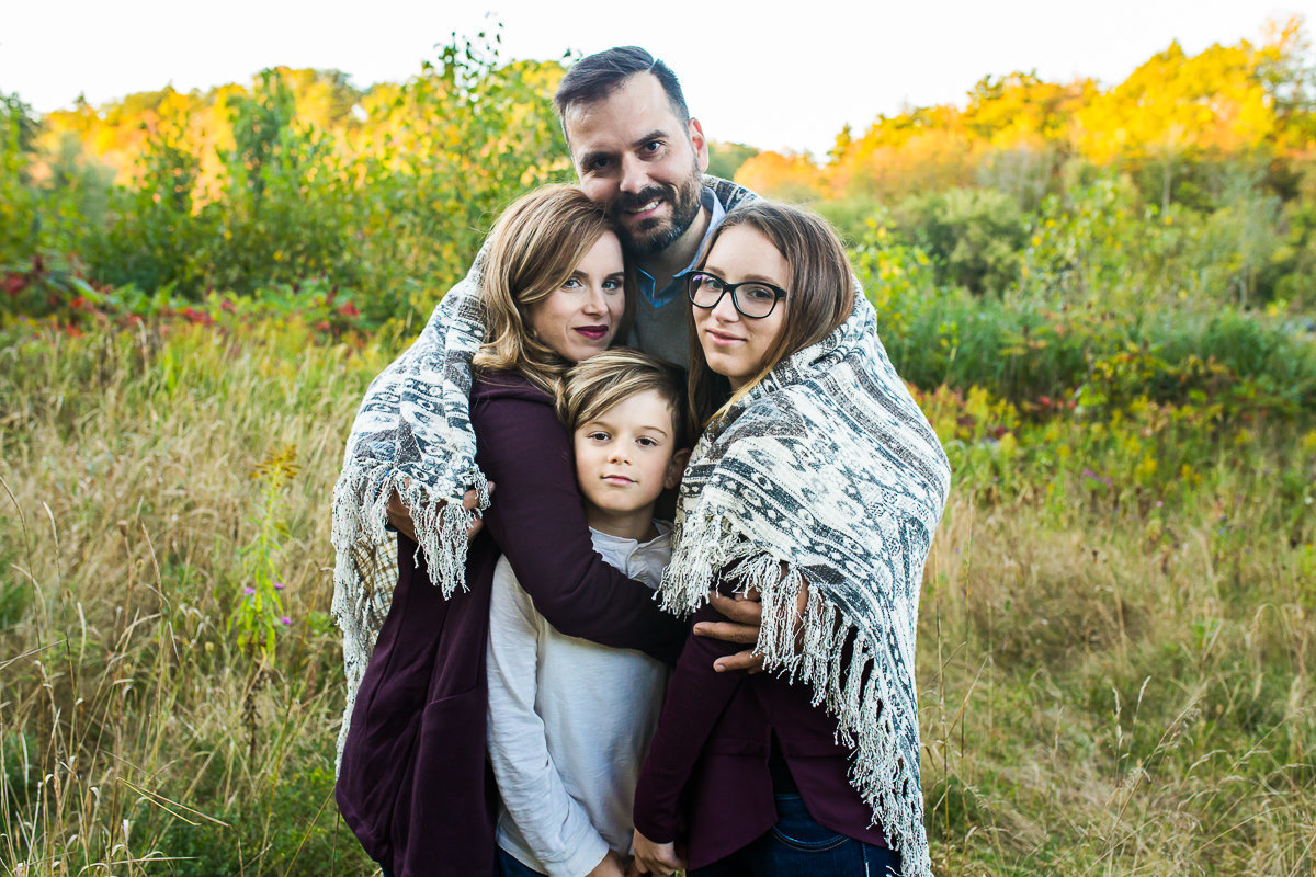Family of four snuggling under blanket {Milton Family Photographer}