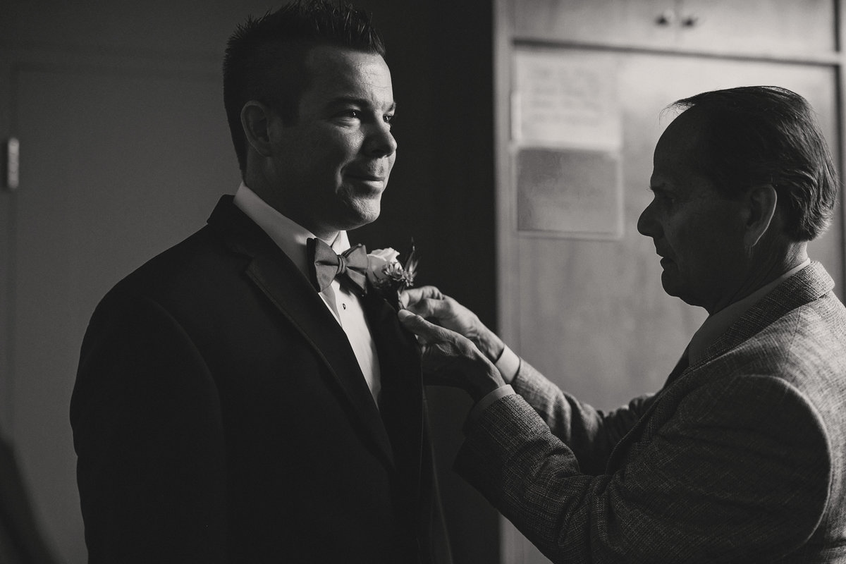black and white candid wedding photography boutonniere groomsman Twin Lakes Golf and Swim club, Oakland, Michigan, wedding photographer Charlene Gurney