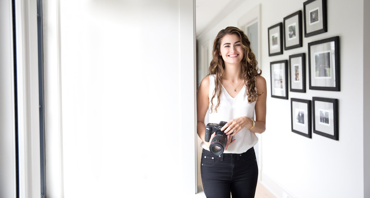 New York photographer poses near framed prints smiling and holding her camera.