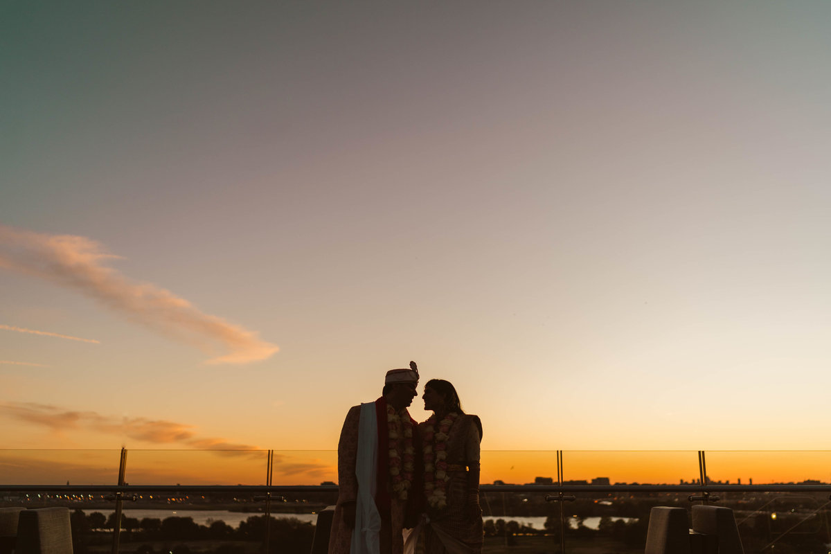 Indian bride and groom standing on rooftop of the Intercontinental wharf at sunset