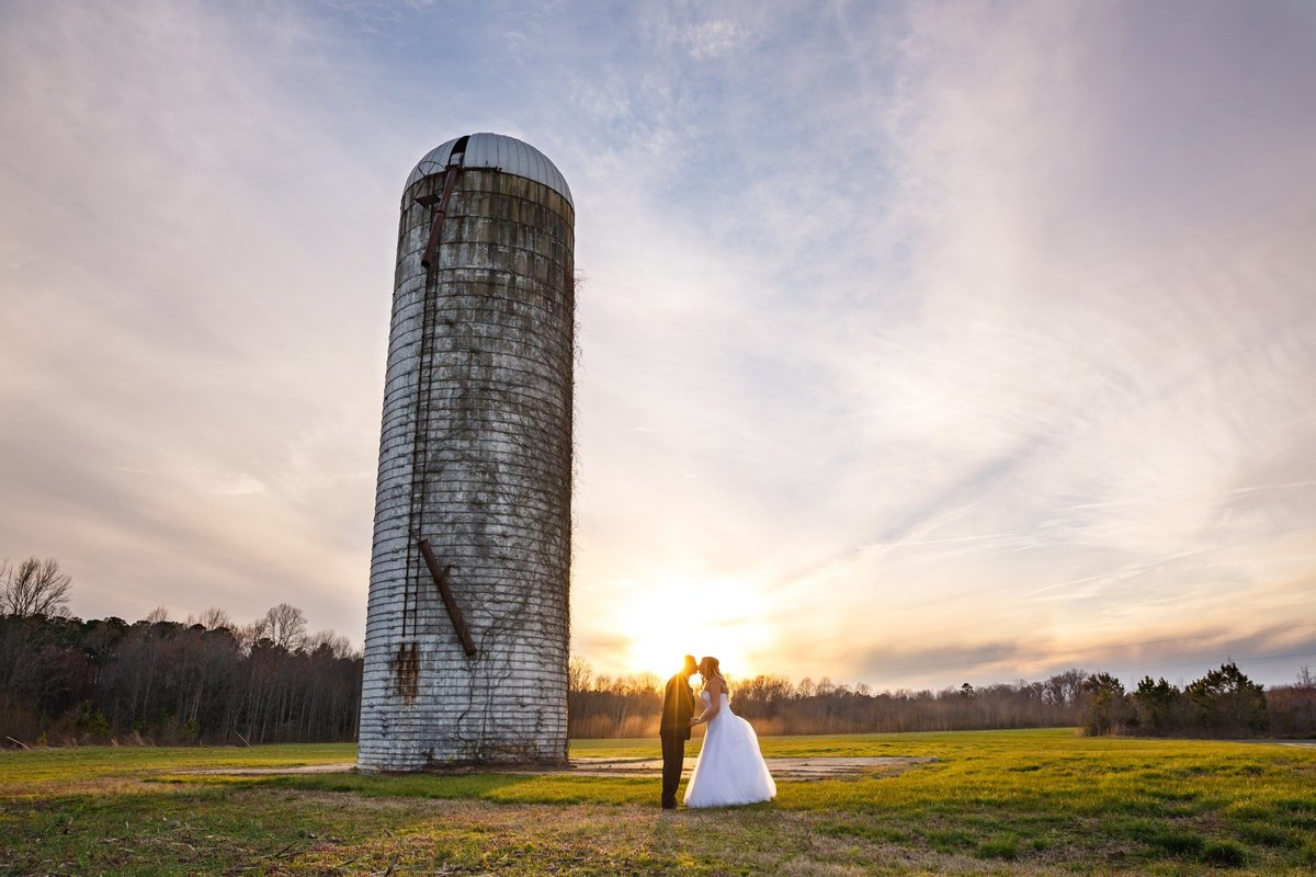 Jennifer Laura Photography bride and groom kiss at sunset by the silo at this Virginia country wedding