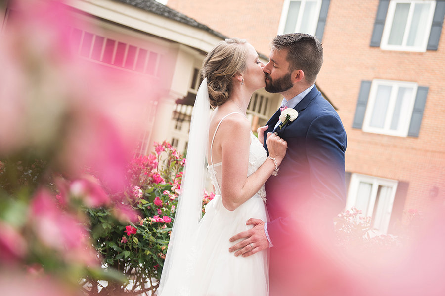 Bride and groom kiss in the courtyard of the Hilton Christiana
