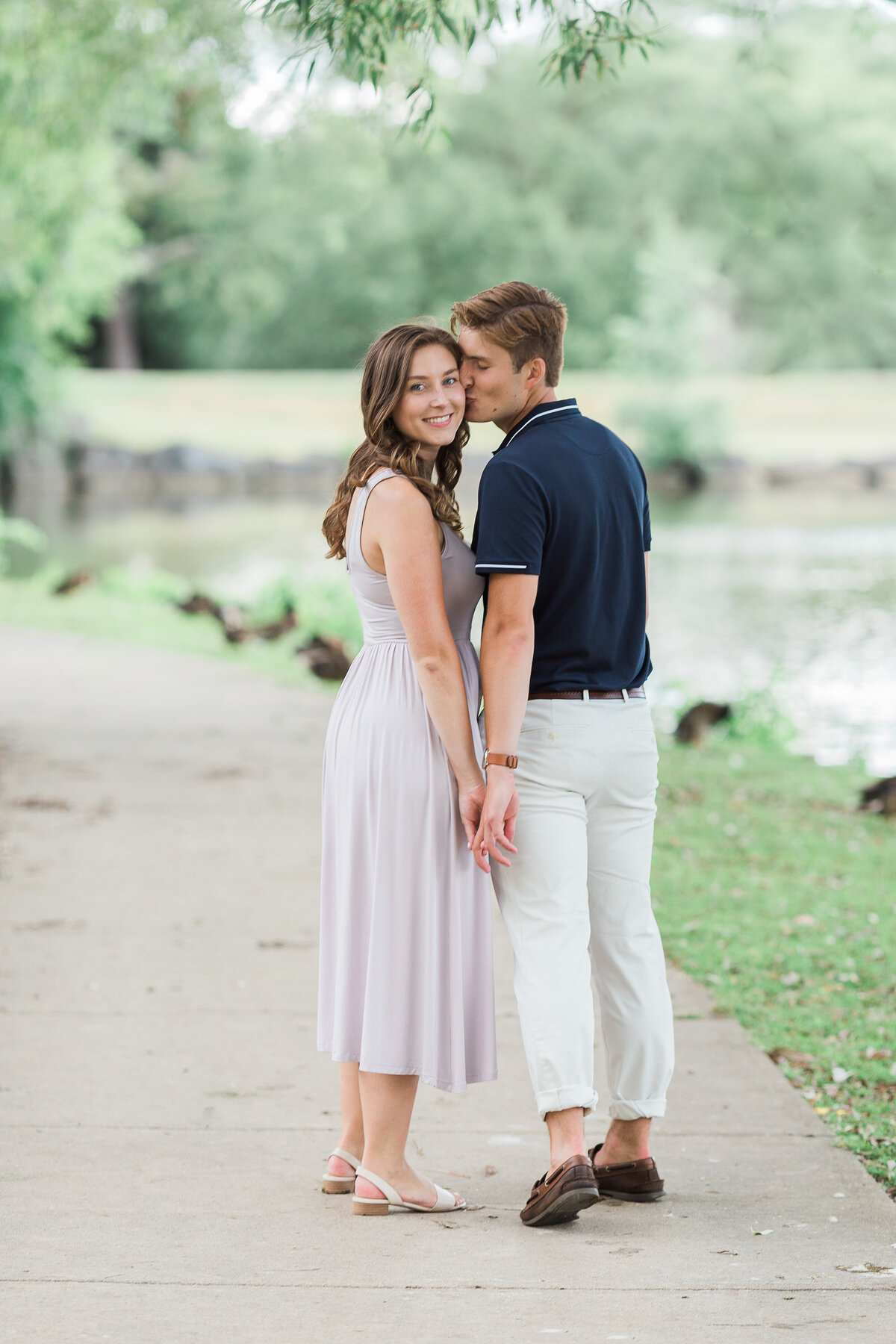 couple holding hands and kissing in engagement photo