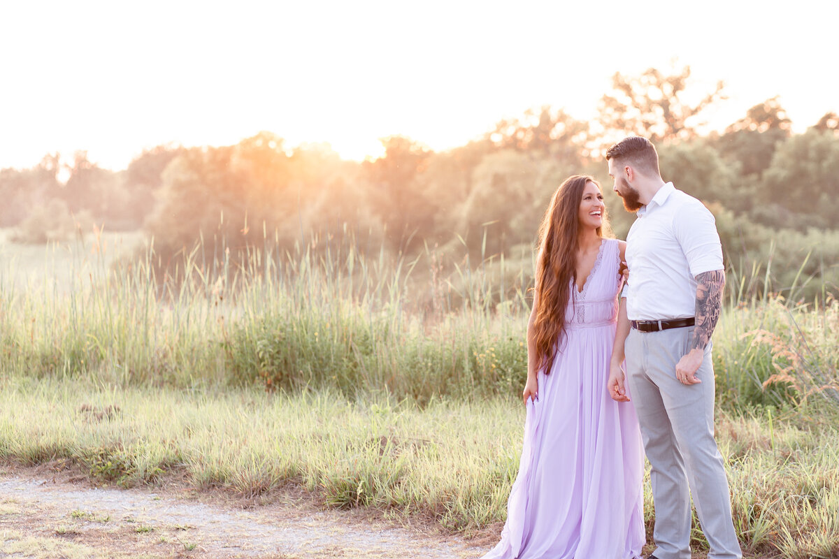 Summer Sunset Romantic Engagement Session guy and girl holding hands and laughing in lavender maxi dress in field on dirt road at Busch Wildlife in St. Louis by Amy Britton Photography Photographer in St. Louis
