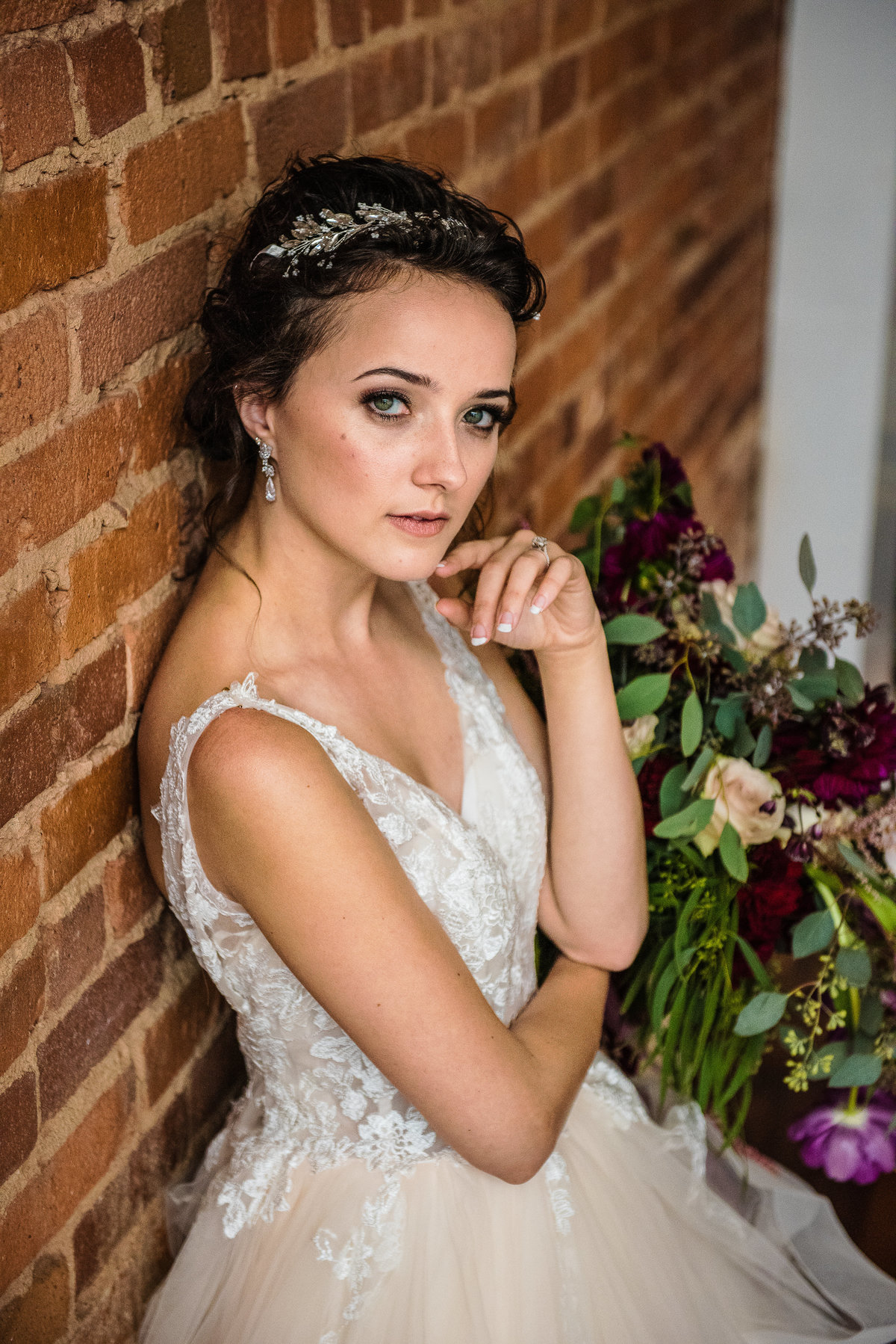 bride with purple flowers leaning on brick wall