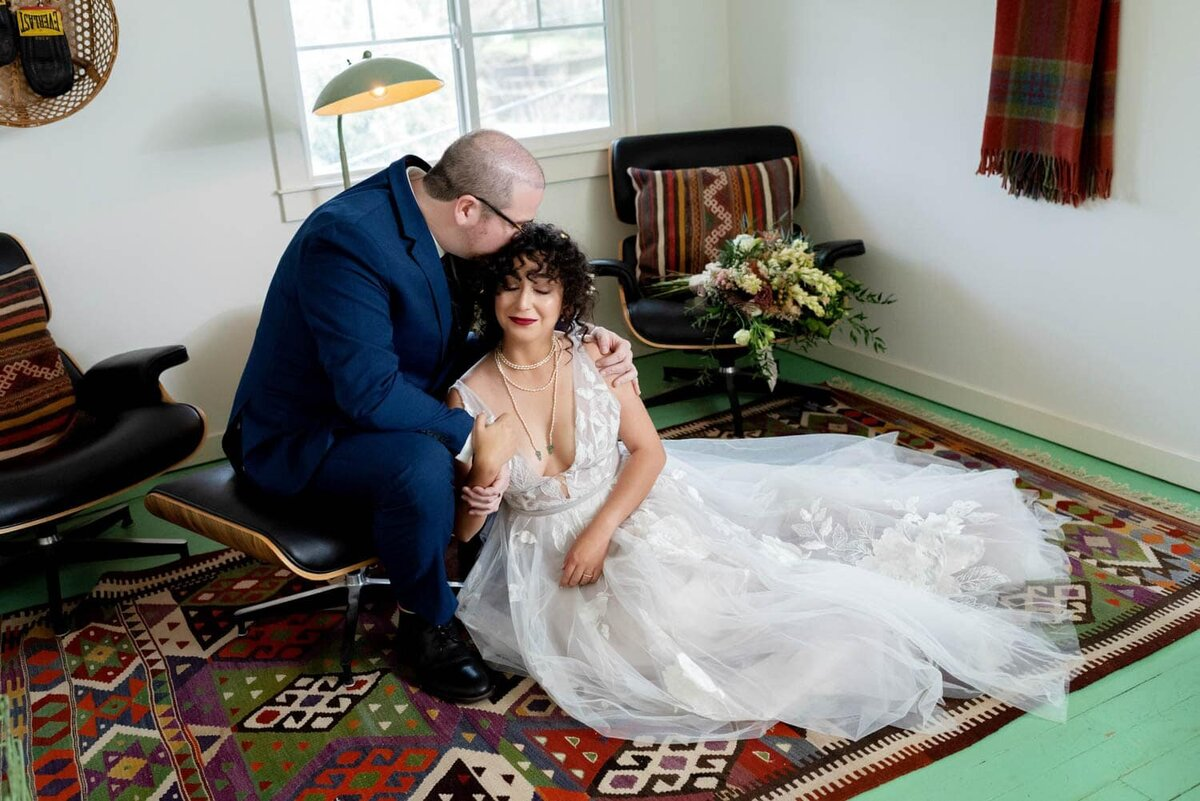 a bride and groom sit on a colorful run and a green hardwood floor and kiss at lodge 902 in hood river