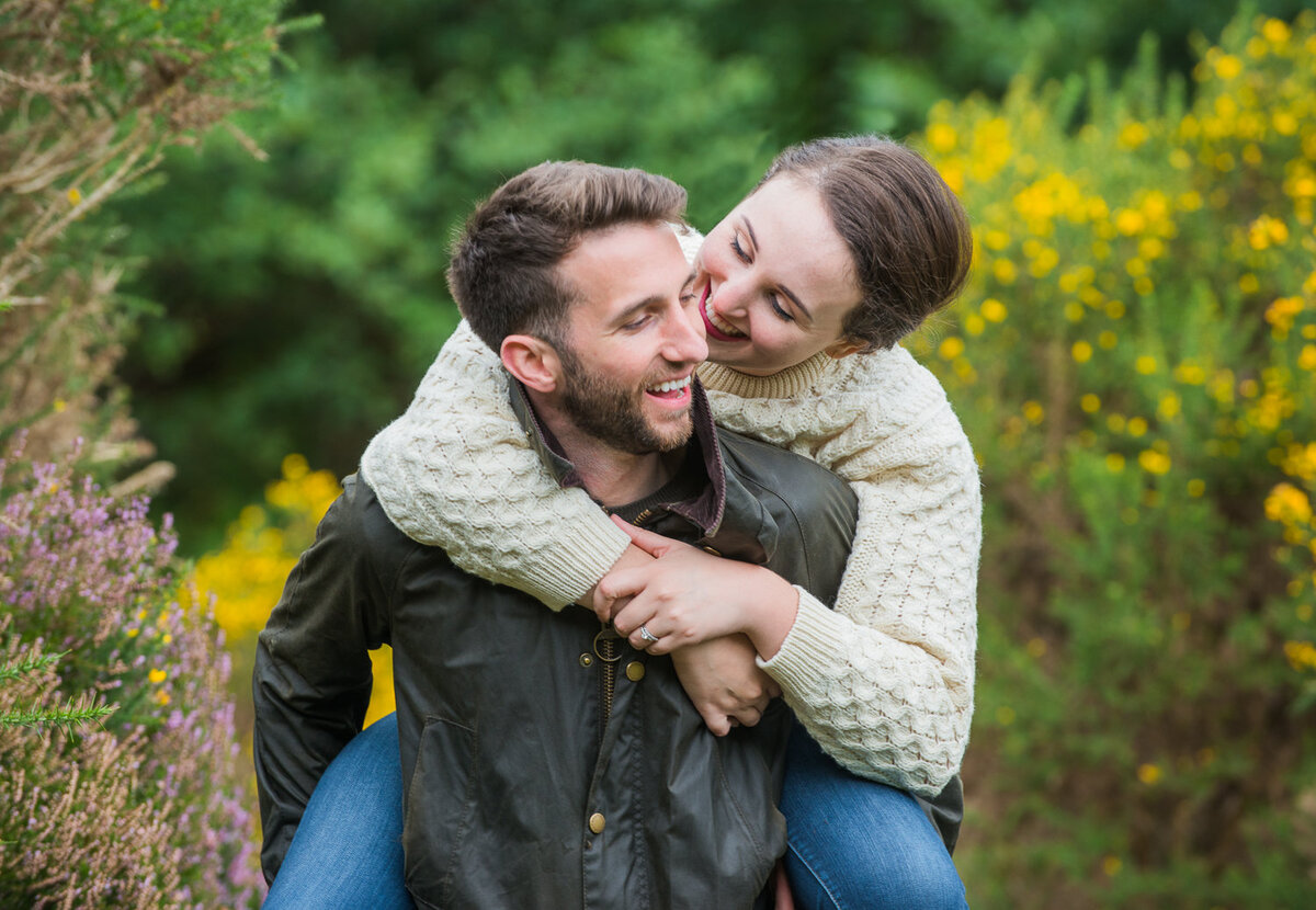 Young couple in wax jacket and aran sweater having fun and surrounded by flowers