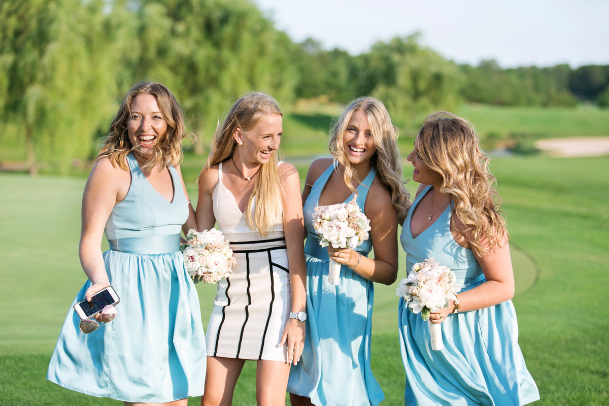 bride and bridesmaids smiling and laughing on golf course at Willow Creek Golf and Country Club