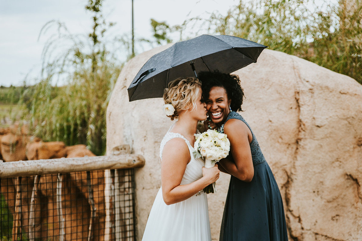 bridesmaid and bride under umbrella at Columbus Zoo in Columbus Ohio