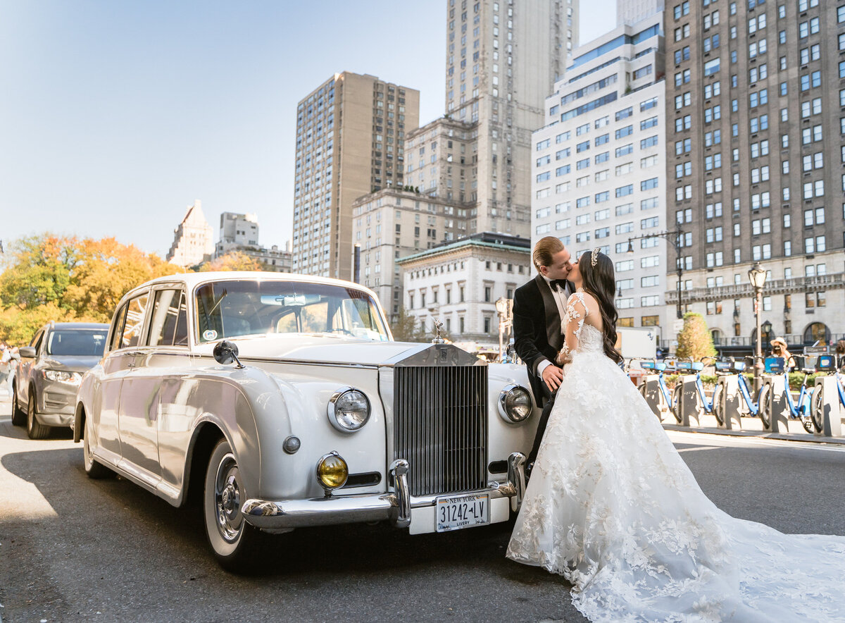 bride and groom in front of limo