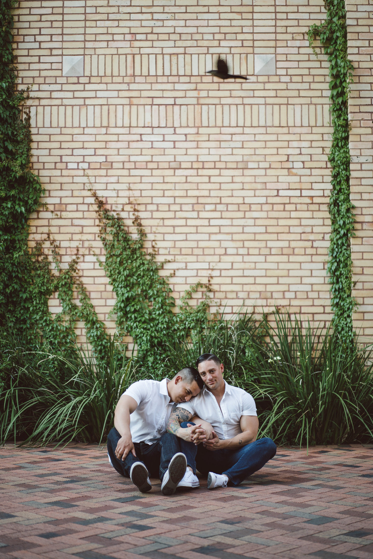 Engaged couple, two men holding each other while sitting on the floor at the Historic Pearl. Same sex engagement session.